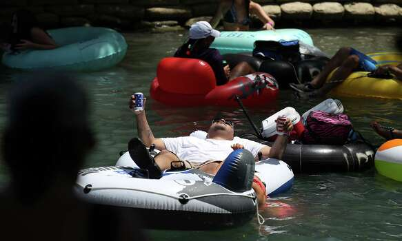 "A tuber holds onto his canned beverages while cruising down the Comal River near Hinman Island Park in New Braunfels on Saturday, July 26, 2014. The 2012 ""can ban"" ordinance was ruled unconstitutional by State District Court Judge Don Burgess in January. Patrons tubing on the river, for now, can bring cans of beverages without breaking any laws while the city of New Braunfels appeals the ruling. Photo: Kin Man Hui, San Antonio Express-News / ©2014 San Antonio Express-News"