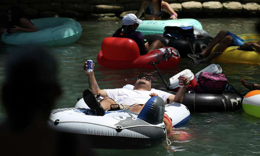 A tuber holds onto his canned beverages while cruising down the Comal River near Hinman Island Park