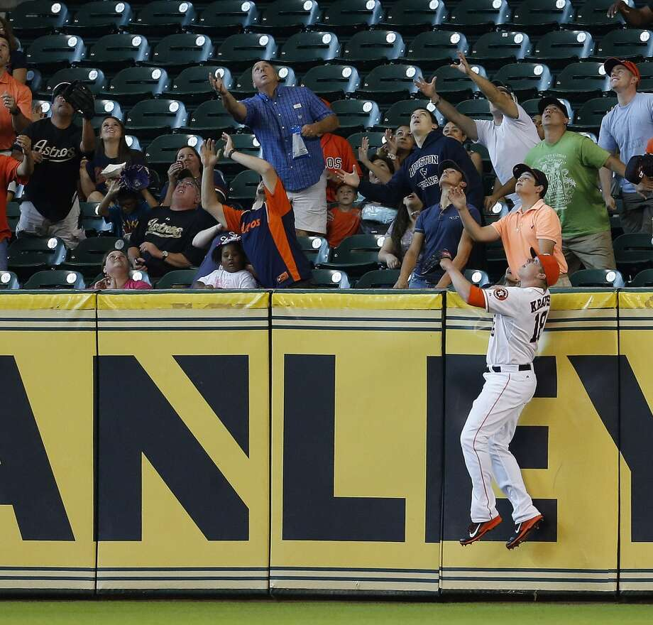 Astros first baseman Marc Krauss (18) leaps up in an effort to get his glove on a home run hit by Marlins first baseman Garrett Jones. Photo: Karen Warren, Houston Chronicle