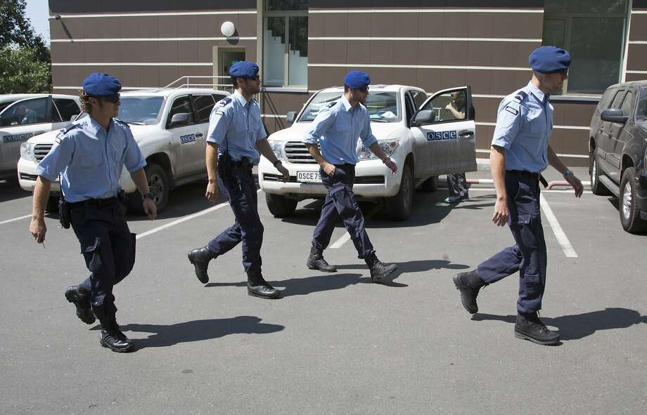 Dutch policemen walk to their cars in the city of Donetsk, eastern Ukraine Sunday, July 27, 2014. A team of international police officers that had been due to visit the site of the Malaysian plane disaster in eastern Ukraine cancelled the trip Sunday after receiving reports of fighting in the area. Alexander Hug, the deputy head of a monitoring team from the OSCE in Europe, said it would be too dangerous for the unarmed mission to travel to the site from its current location in the rebel-held city of Donetsk. (AP Photo/Dmitry Lovetsky) Photo: Dmitry Lovetsky, Associated Press