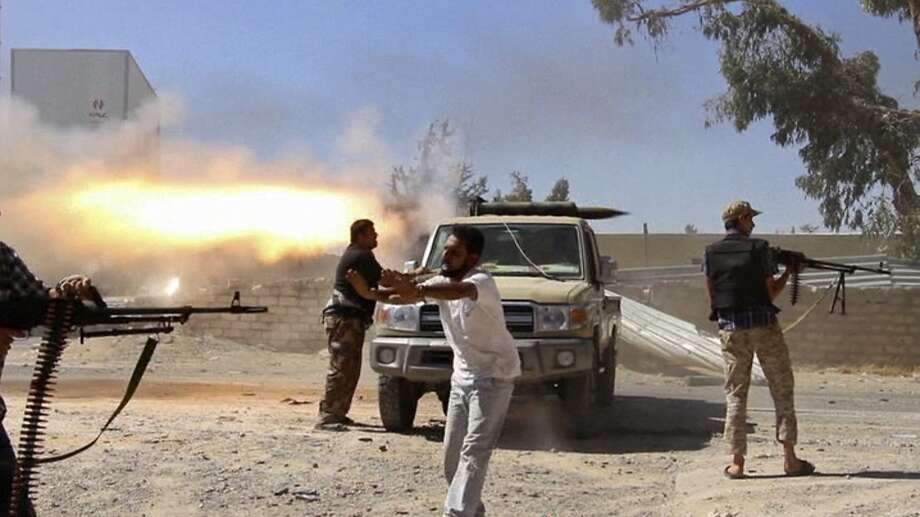 Fighters from the Islamist Misarata brigade fire toward Tripoli's international airport Saturday in an attempt to seize control from a powerful rival militia. The battle for control of the airport has been going on for about two weeks. Photo: Uncredited, Associated Press