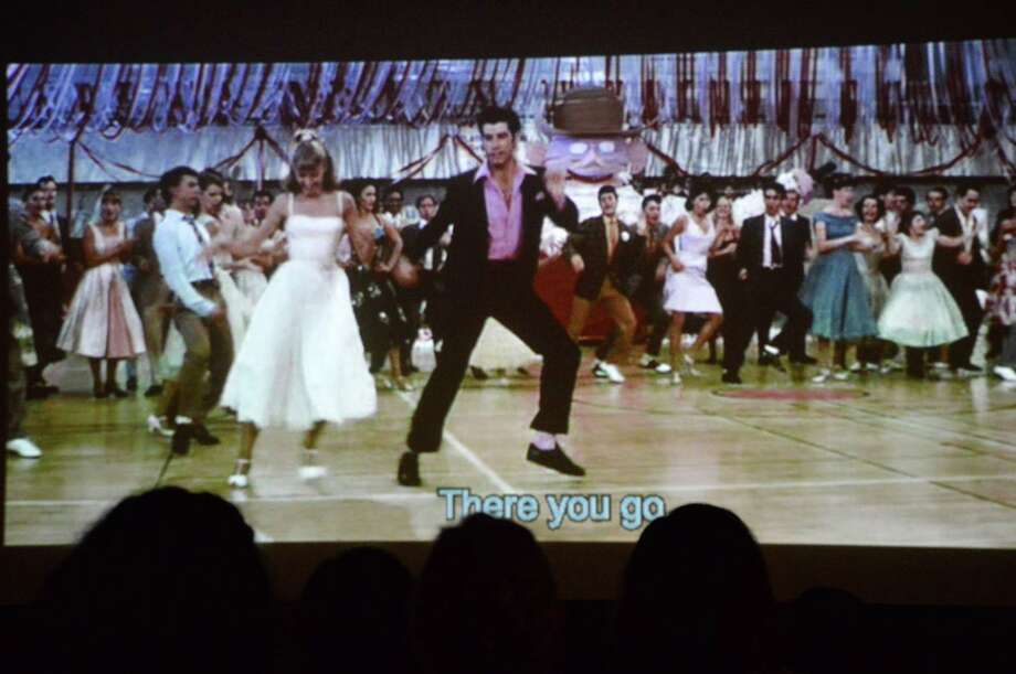 "As part of the ""Rockin' Rydell"" edition of the ""Grease"" screening, all the songs featured lyrics so the audience could join in. Photo: Jarret Liotta / Westport News"