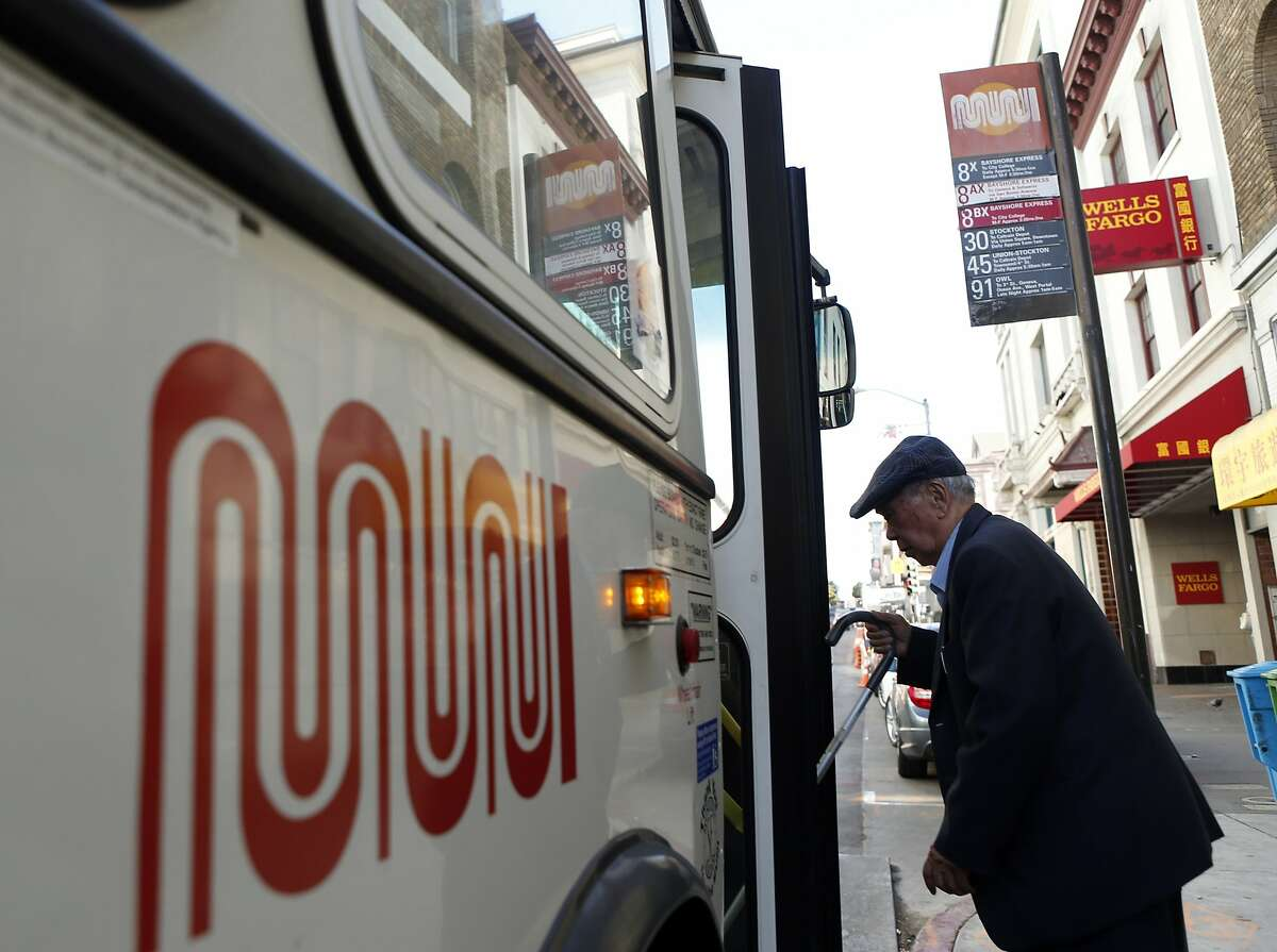 A MUNI rider boards a bus at a Stockton Street bus stop on Thursday, July 24, 2014, in San Francisco, Calif..