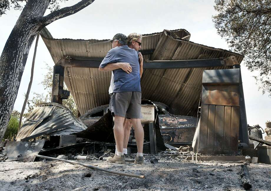 Bill Cleek (left) hugs Terry Cromwell, who owned 13 antique cars destroyed by fire on the Rancho Cicada Retreat property in Plymouth. Photo: Randy Pench, The Sacramento Bee