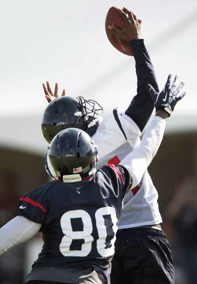 Veteran cornerback Johnathan Joseph shows his physical status after having toe surgery late last season shouldn't be a concern by leaping to intercept a pass intended for Andre Johnson (80) during the Texans' practice Sunday. Photo: Brett Coomer, Staff / © 2014 Houston Chronicle
