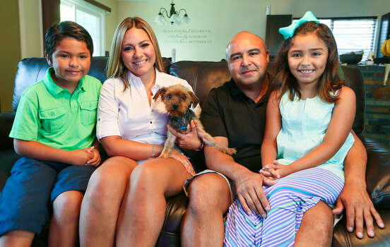 Brody joins Aidan (from left), Yvette Castillo, Juan Delgado and Leila after the Yorkshire terrier went missing for more than a year, a loss complicated by the family moving. Photo: Marvin Pfeiffer / San Antonio Express-News / EN Communities 2014