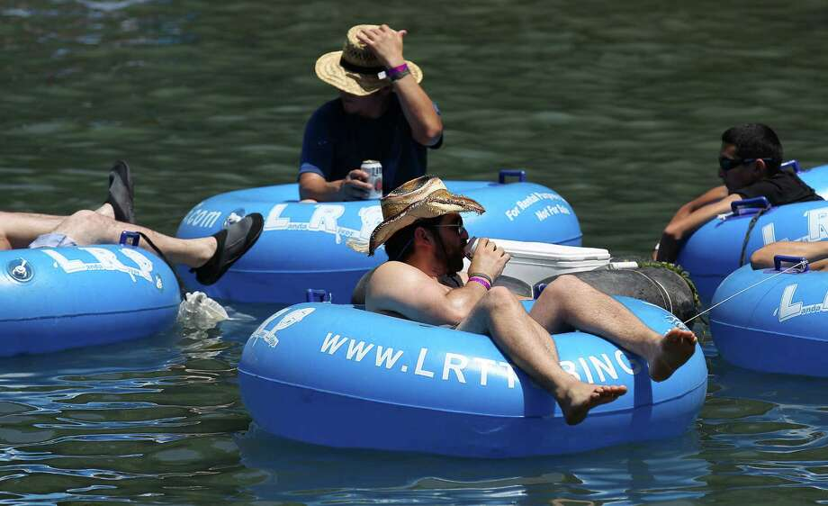 "A tuber takes a sip from his canned drink while floating the Comal River near Hinman Island Park in New Braunfels on Saturday, July 26, 2014. The 2012 ""can ban"" ordinance was ruled unconstitutional by State District Court Judge Don Burgess in January. Patrons tubing on the river, for now, can bring cans of beverages without breaking any laws while the city of New Braunfels appeals the ruling. Photo: Kin Man Hui, San Antonio Express-News / ©2014 San Antonio Express-News"