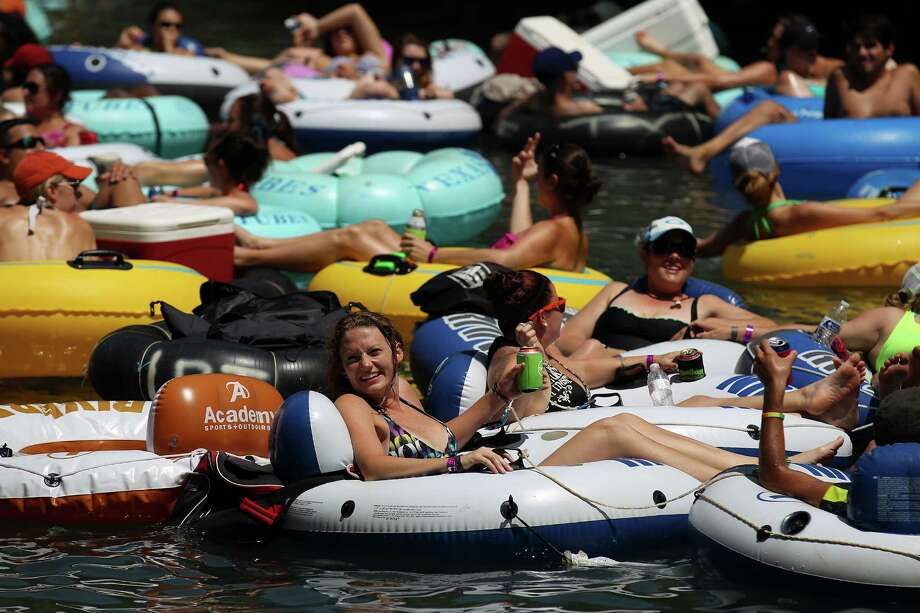 "Tubers take to the Comal River near Hinman Island Park in New Braunfels on Saturday, July 26, 2014. The 2012 ""can ban"" ordinance was ruled unconstitutional by State District Court Judge Don Burgess in January. Patrons tubing on the river, for now, can bring cans of beverages without breaking any laws while the city of New Braunfels appeals the ruling. Photo: Kin Man Hui, San Antonio Express-News / ©2014 San Antonio Express-News"