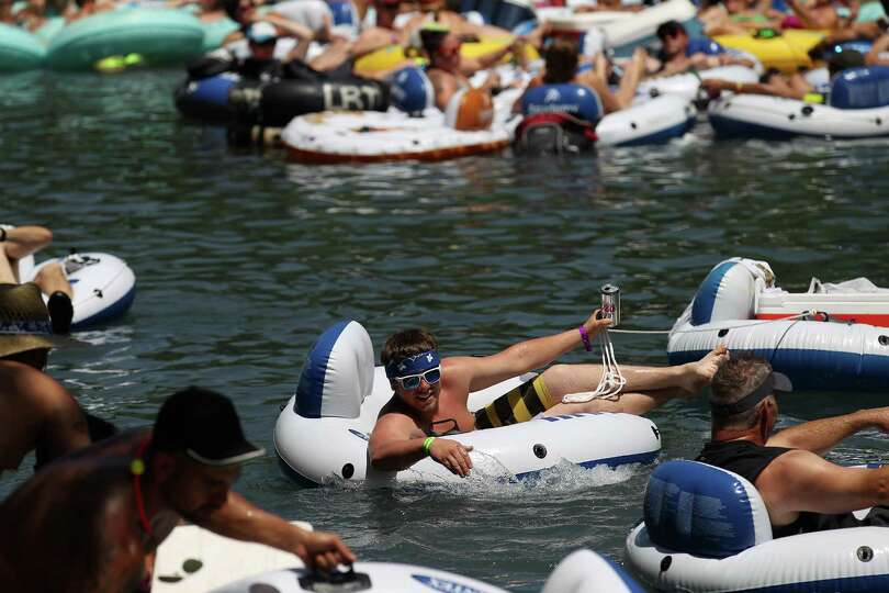A tuber holds onto his canned beverage while floating the Comal River near Hinman Island Park in New