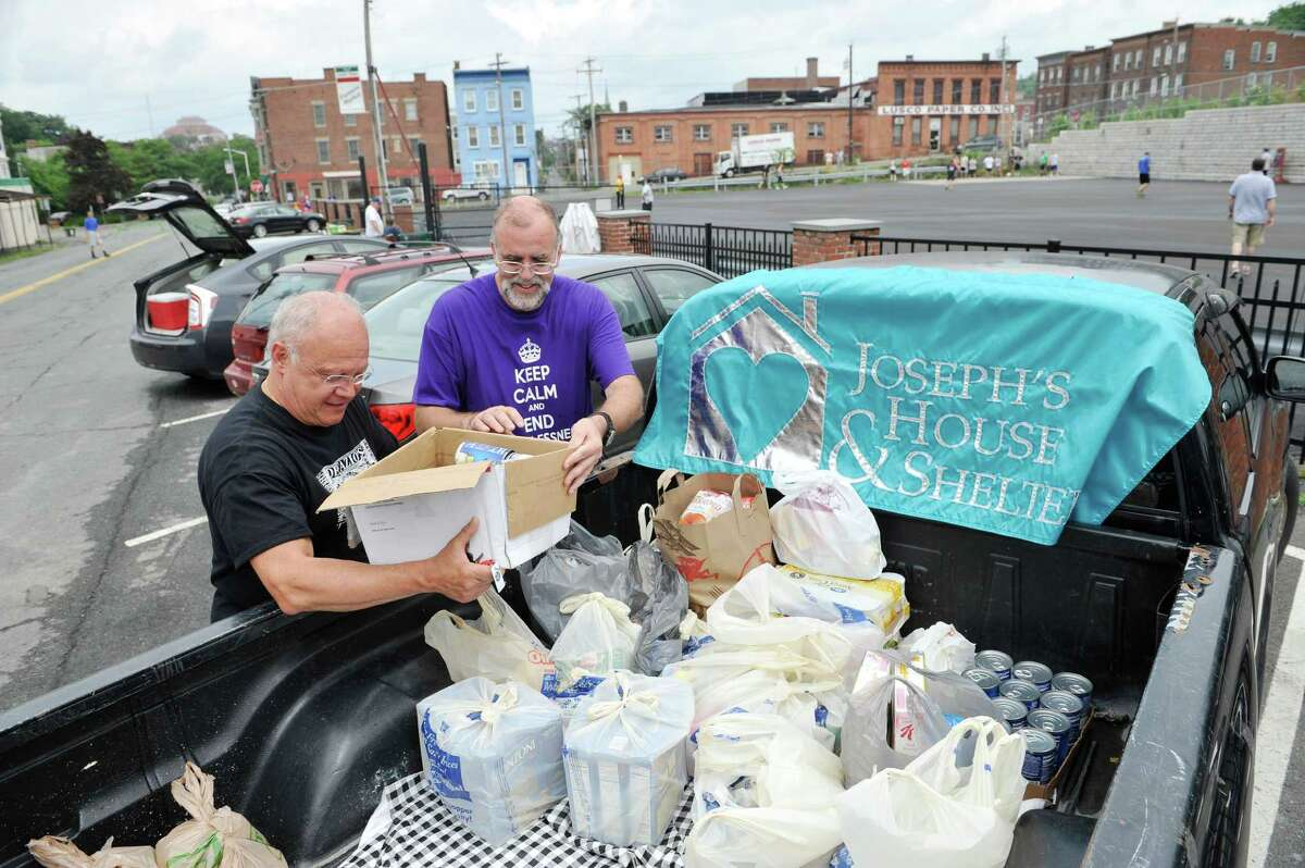 Rocco DeFazio, left, owner of DeFazio's Pizza, and Kevin O'Connor, executive director of Joseph's House, place some donated food into a truck at the Stick it to Hunger sixth annual stick ball tournament on Sunday, July 27, 2014, in Troy, N.Y. The event is put on by the Friends of Little Italy and the DeFazio Family. Teams playing in the games bring food items to donate to Joseph's House and Shelter in Troy. Rocco DeFazio, said that the event began as a way to raise awareness and to help feed the children in homeless families.