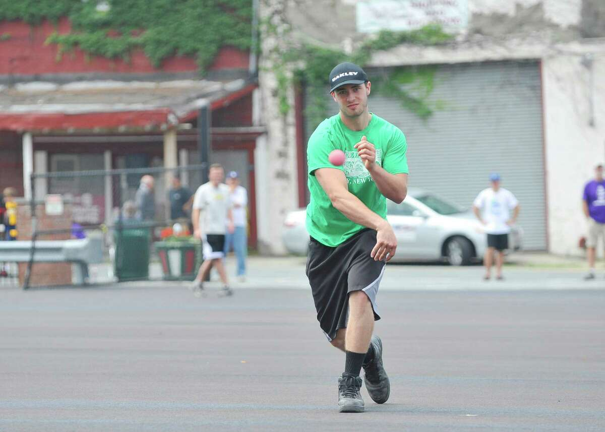 Tim Yetto, playing for Team Money, pitches to a Team DeFazio player during the Stick it to Hunger sixth annual stick ball tournament on Sunday, July 27, 2014, in Troy, N.Y. The event is put on by the Friends of Little Italy and the DeFazio Family. Teams playing in the games bring food items to donate to Joseph's House and Shelter in Troy. Rocco DeFazio, owner of DeFazio's Pizza, said that the event began as a way to raise awareness and to help feed the children in homeless families.