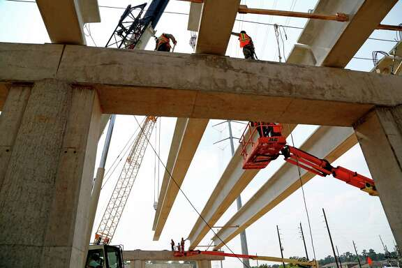 A 123,000-pound girder is placed on the Rothwood Road bridge in Spring along the Grand Parkway.