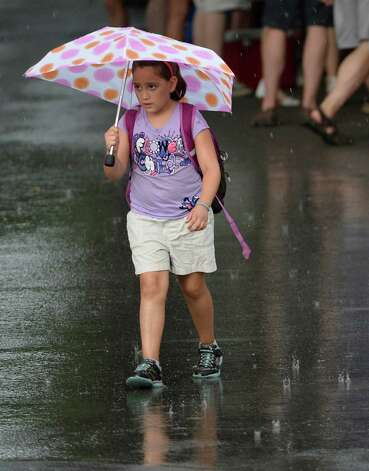 A young race patron dodges the rain drops during a brief storm Sunday afternoon July 27, 2014 at the Saratoga Race Course in Saratoga Springs, N.Y.    (Skip Dickstein / Times Union) Photo: SKIP DICKSTEIN