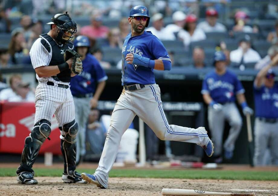 New York Yankees catcher Francisco Cervelli, left, looks down as Toronto Blue Jays Jose Bautista scores on Dioner Navarro's  game-winning, ninth-inning RBI single in a baseball game against the New York Yankees at Yankee Stadium in New York, Sunday, July 27, 2014.   The Jays defeated the Yankees 5-4. (AP Photo/Kathy Willens) ORG XMIT: NYY117 Photo: Kathy Willens / AP