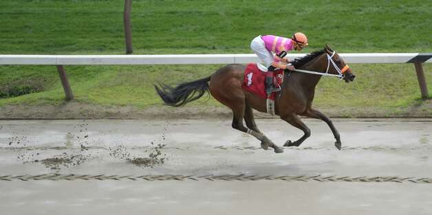 Sunday Sonnet with jockey Jose Ortiz glides above the mud to win the first race Sunday afternoon July 27, 2014 at the Saratoga Race Course in Saratoga Springs, N.Y.    (Skip Dickstein / Times Union) Photo: SKIP DICKSTEIN