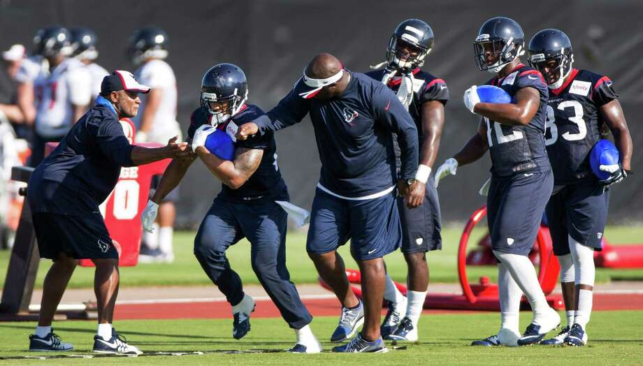 Running back Arian Foster, left, participates in a drill Sunday before leaving practice early with a leg ailment that is not believed to be serious. Foster missed eight games during the 2013 season due to a back injury. Photo: Brett Coomer, Staff / © 2014 Houston Chronicle