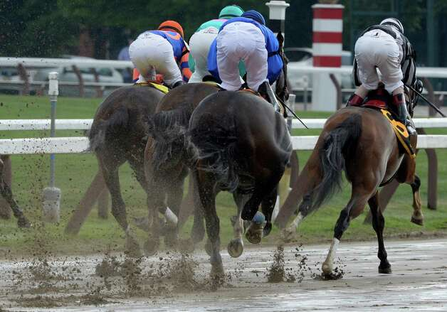 Mud flies from the hooves of the field of feature race of the day, The Shuvee Sunday afternoon July 27, 2014 at the Saratoga Race Course in Saratoga Springs, N.Y.    (Skip Dickstein / Times Union) Photo: SKIP DICKSTEIN