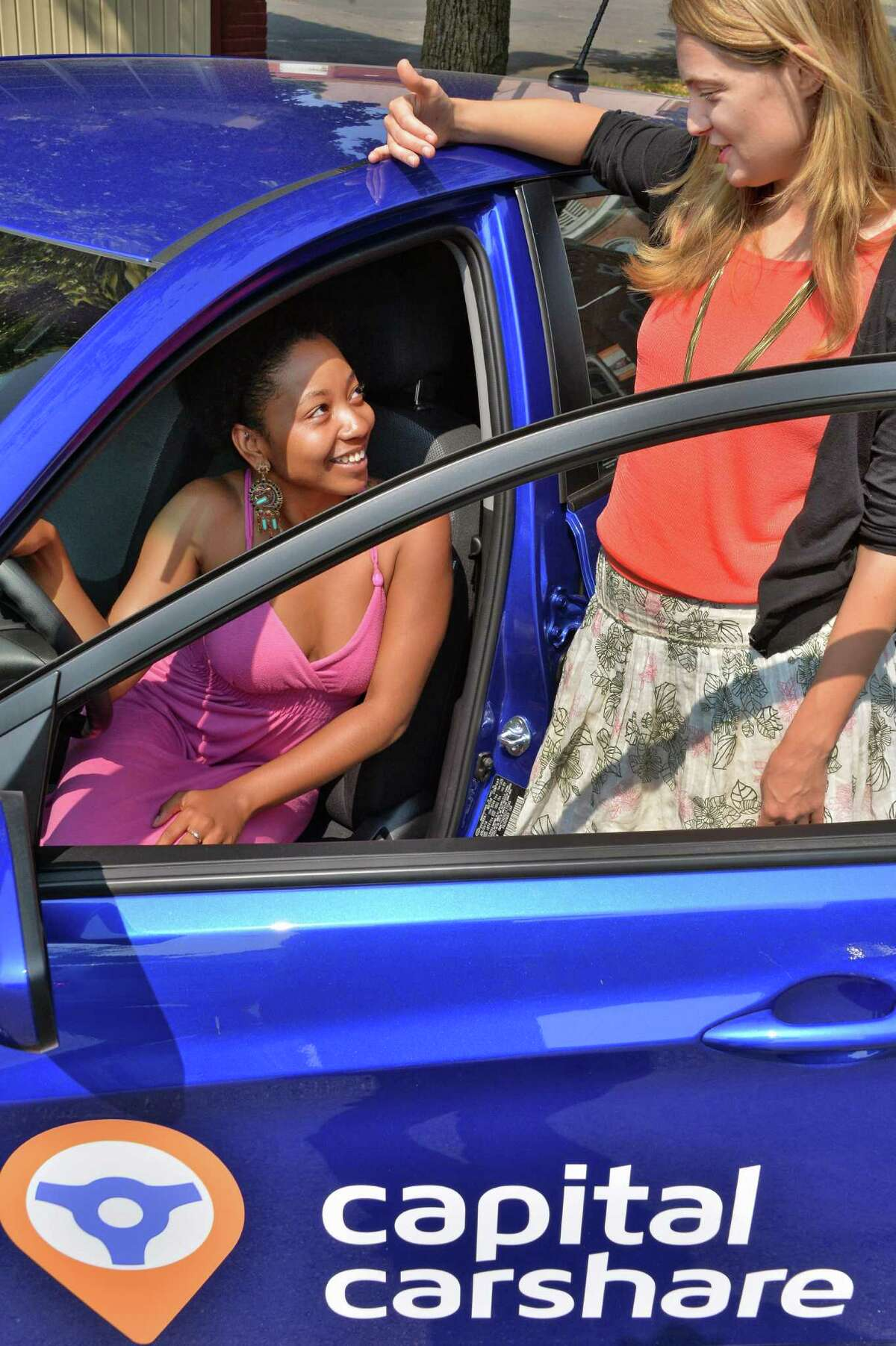 Capital CarShare's Nnenna Ferguson, left, and Kate Lawrence of the Mayor's Office of Energy and Sustainability with a Hyundai Accent, one of four vehicles now in their fleet, Friday July 25, 2014, in Albany, NY. (John Carl D'Annibale / Times Union)