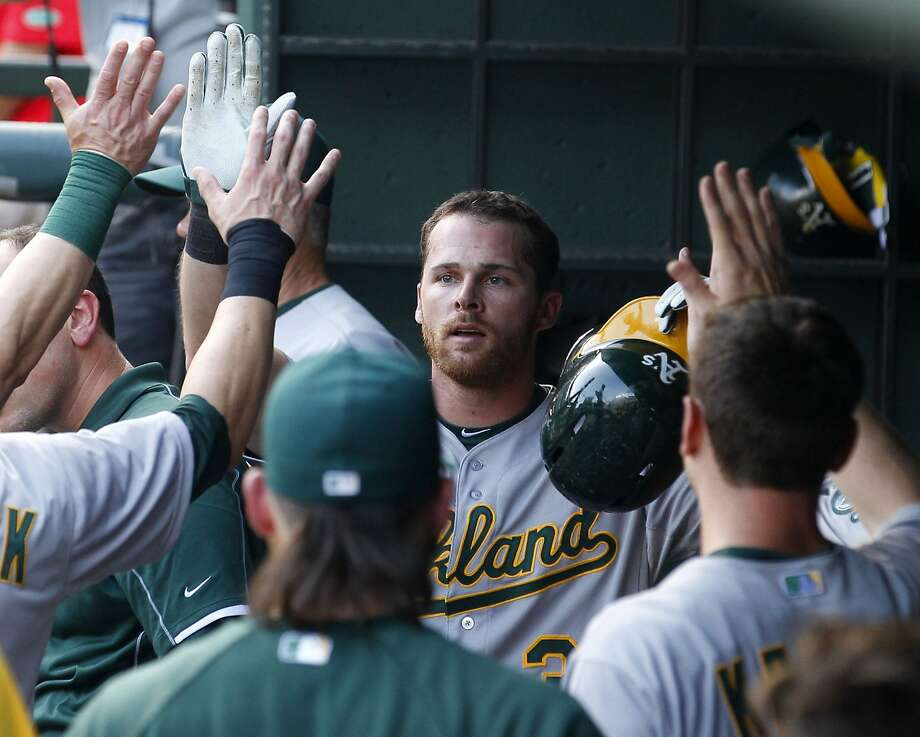 Craig Gentry (facing camera) gets high fives from his teammates after scoring the third of five second-inning runs. Photo: Richard W. Rodriguez, McClatchy-Tribune News Service