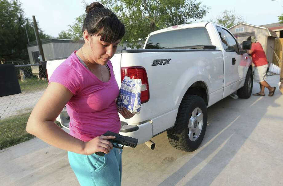 Ashlee Ann Villarreal, 24, shows her 9 mm handgun at the home of her fiance's parents in La Joya, not far from the Rio Grande. She and her fiance, Jesus Cantu, 27, carry guns for personal protection. / @San Antonio Express-News