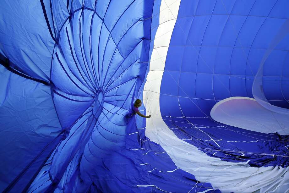 A crew member checks guide wires as a hot air balloon inflates for flight at the 32nd annual OuickChek New Jersey Festival of Ballooning Sunday, July 27, 2014, in Readington, N.J. (AP Photo/Mel Evans) Photo: Mel Evans, Associated Press