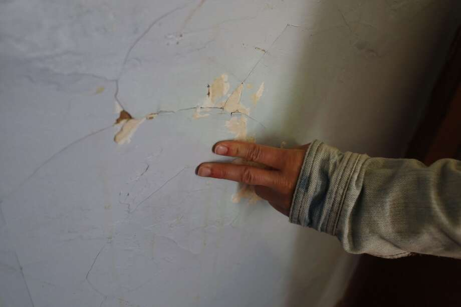 Community Organizer with the Central City SRO Collaborative Karin Drucker runs her fingers over a cracked wall at The Best hotel in San Francisco, Calif. Photo: Mike Kepka