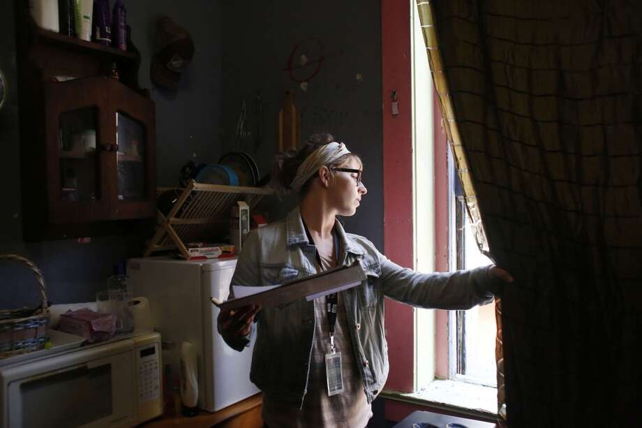 Community Organizer with the Central City SRO Collaborative Karin Drucker investigates the window in a tenants room at the Lawrence Hotel in San Francisco, Calif. Photo: Mike Kepka