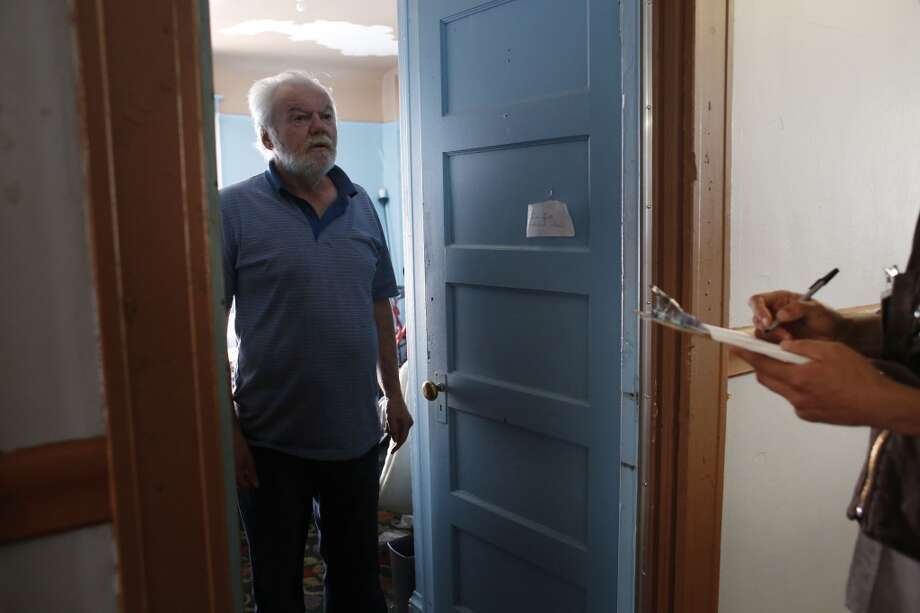 With a bedbug survey in his hand, JC Castle, Tenant organizer with the Central City SRO Collaborative, meets with  Ellis hotel resident Tom Donahue in San Francisco, Calif. Photo: Mike Kepka