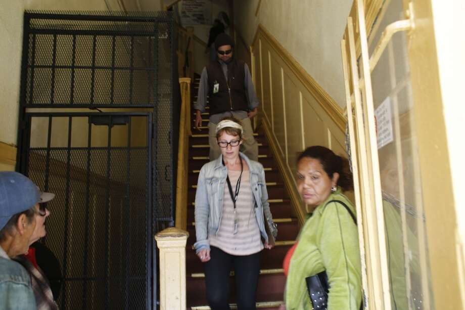 Trying to check for a potential code violations, Community Organizer with the Central City SRO Collaborative Karin Drucker with tenant organizer JC Castle are asked to leave a 6th Street SRO hotel in San Francisco, Calif. Photo: Mike Kepka