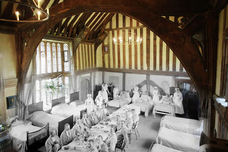 In this digital composite image a comparison has been made of Great Dixter, England during World War I and modern day 2014: Soldiers and nurses at Great Dixter, Northiam, East Sussex, WWI, 1916. Soldiers at table in the Great Hall at Great Dixter, with some still in bed. The medieval beams and mullioned window are clearly visible. Great Dixter was turned into a convalescent home for soldiers in the 1st World War, a few years after Lutyens had worked on the house for Nathaniel Lloyd. on July 16, 2014 in Great Dixter, England. Photo: Heritage Images, Heritage Images/Getty Images / Reproduced by permission of English Heritage / Heritage-Images