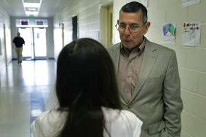South San Antonio ISD Superintendent Dr. Abelardo Saavedra, right, talks with an 8th grade student as he visits Zamora Middle School. Friday, March 28, 2014.
