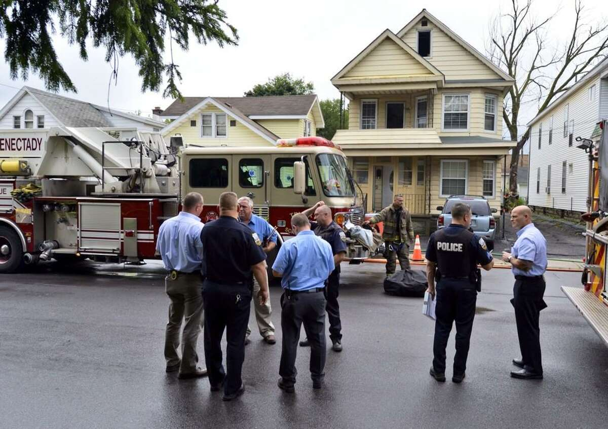 A group of detectives gather as they start the investigation of a fire at 322-324 Michigan Ave. in Schenectady. (Skip Dickstein/Times Union)