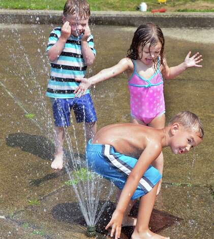 Watervliet children, from left, Mike Campagna, 4, Lily McFee, 3, and Alex Sluus, 4, cool off in the spray pool at Seventh Street Park Friday July 25, 2014,in Watervliet, NY.  (John Carl D'Annibale / Times Union) Photo: John Carl D'Annibale, Albany Times Union