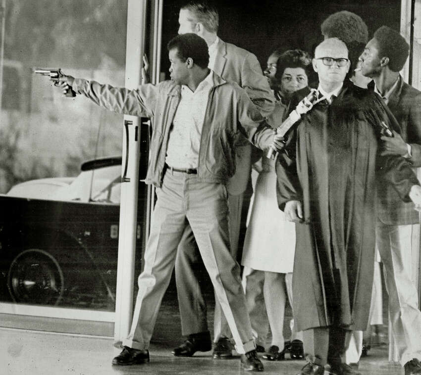 Convict James McClain points a revolver down the hall as he holds a handmade weapon that is taped to the neck of Judge Harold J. Haley on August 7, 1970. This photo was made just before the shootout during this escape attempt from the Marin County Hall of Justice. Behind McClain is Deputy D.A> Gary Thomas. Woman at center is Mrs. Elena Graham. Behind Graham is convict William Christmas. At right holding pistol is convict Russell Magee. Superior Court judge Harold Haley was killed in the shootout.