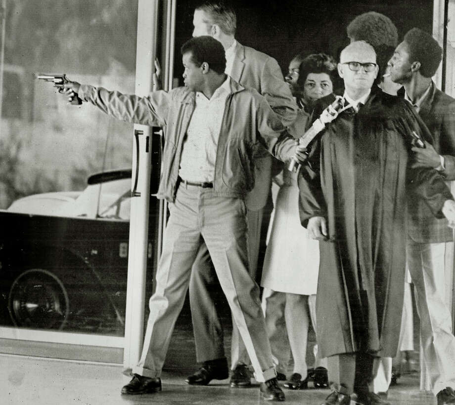 Convict James McClain points a revolver down the hall as he holds a handmade weapon that is taped to the neck of Judge Harold J. Haley on August 7, 1970. This photo was made just before the shootout during this escape attempt from the Marin County Hall of Justice. Behind McClain is Deputy D.A> Gary Thomas. Woman at center is Mrs. Elena Graham. Behind Graham is convict William Christmas. At right holding pistol is convict Russell Magee.  Superior Court judge Harold Haley was killed in the shootout. Photo: Roger Bockrath / San Rafael Independent Journal