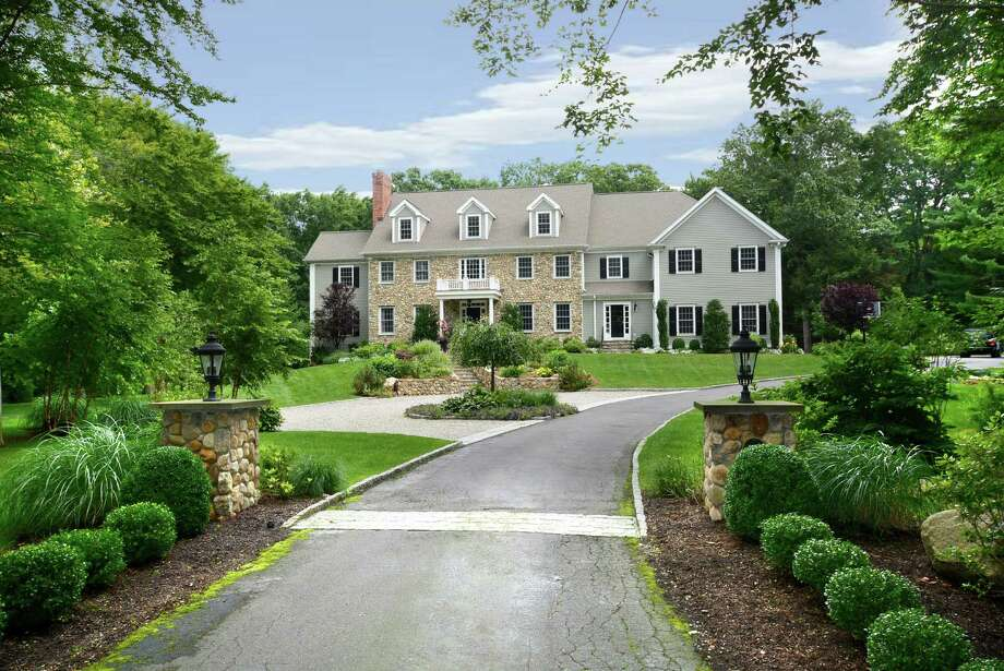 The stone-and-shingle Colonial, with nearly 7,000 square feet of  living space, is located at the edge of town, at the Wilton-New Canaan border. It is on the market for $2,295,000. Photo: Contributed Photo, Contributed / New Canaan News Contributed