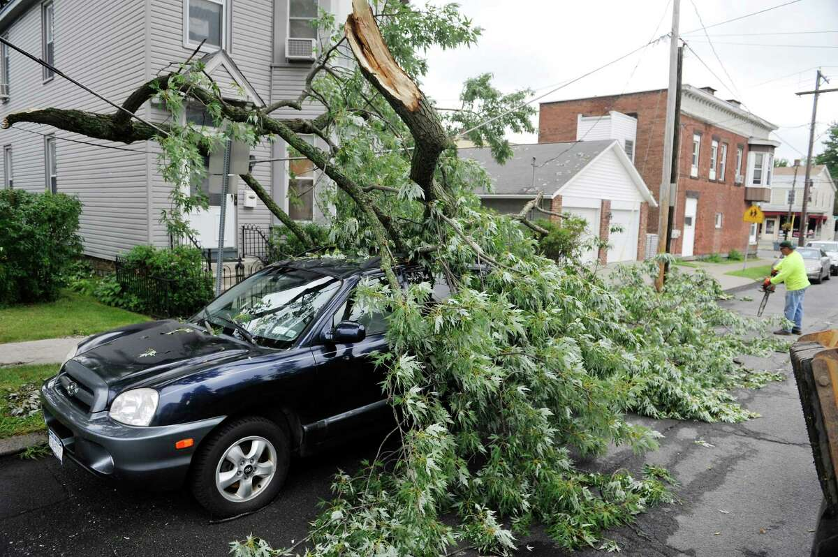 Crews clean up a tree branch Monday, July 28, 2014, that came down on a car parked on Seventh Ave. Sunday in Watervliet, N.Y. A strong storm came through the area Sunday afternoon causing some damage. (Paul Buckowski / Times Union)