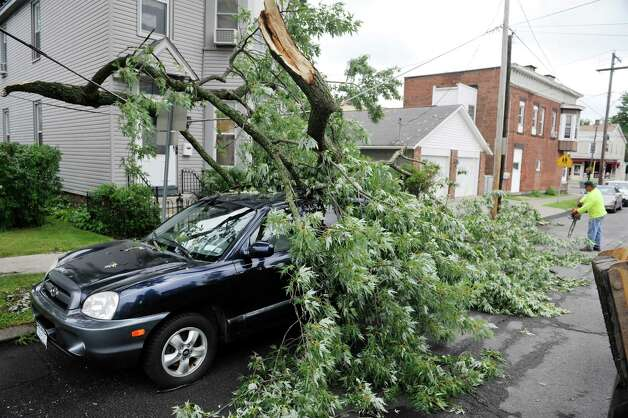 Crews clean up a tree branch Monday, July 28, 2014, that came down on a car parked on Seventh Ave. Sunday in Watervliet, N.Y. A strong storm came through the area Sunday afternoon causing some damage.  (Paul Buckowski / Times Union) Photo: Paul Buckowski / 00027959A