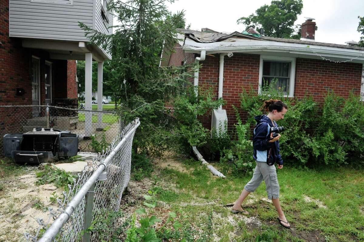 Rachel Lewis takes pictures of the damage done to her home at 555 Fourth Ave. on Monday, July 28, 2014, after a large tree in her neighbor's yard came down on her home Sunday in Watervliet, N.Y. on Sunday afternoon. The stump of the tree is seen on the left in the photograph. (Paul Buckowski / Times Union)