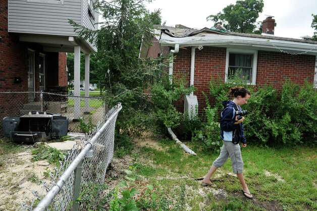 Rachel Lewis takes pictures of the damage done to her home at 555 Fourth Ave. on Monday, July 28, 2014, after a large tree in her neighbor's yard came down on her home Sunday in Watervliet, N.Y. on Sunday afternoon. The stump of the tree is seen on the left in the photograph.  (Paul Buckowski / Times Union) Photo: Paul Buckowski / 00027959A