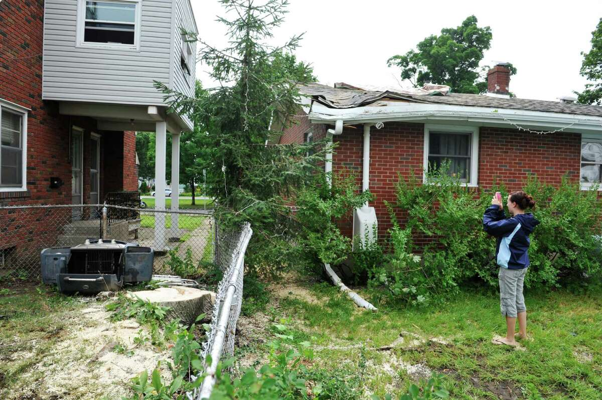 Rachel Lewis takes pictures of the damage done to her home at 555 Fourth Ave. on Monday, July 28, 2014, after a large tree in her neighbor's yard came down on her home Sunday afternoon in Watervliet, N.Y. The stump of the tree is seen on the left in the photograph. (Paul Buckowski / Times Union)