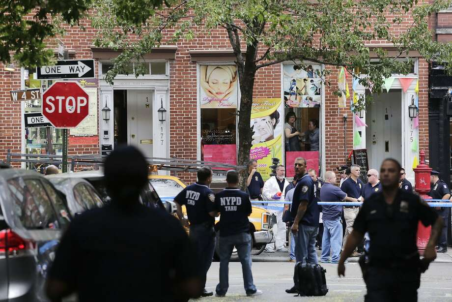 Officers guard the scene of the shooting in the Greenwich Village neighborhood of New York City. Photo: Mark Lennihan, Associated Press