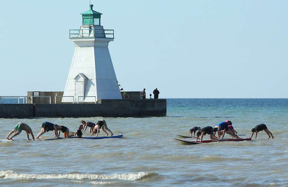 If yoga on dry land isn't difficult enoughfor you, try it while balancing on a paddleboard. Stand-up paddleboard   yoga classes meet by the lighthouse in Port Dover, Ontario. Photo: Dave Chidley, Associated Press