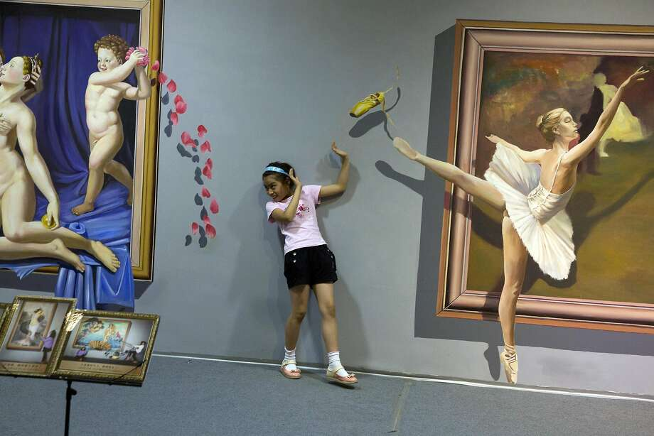 Off-the-wall art: A girl ducks out of the way of a flying ballerina slipper at an exhibition of 3-D paintings in 