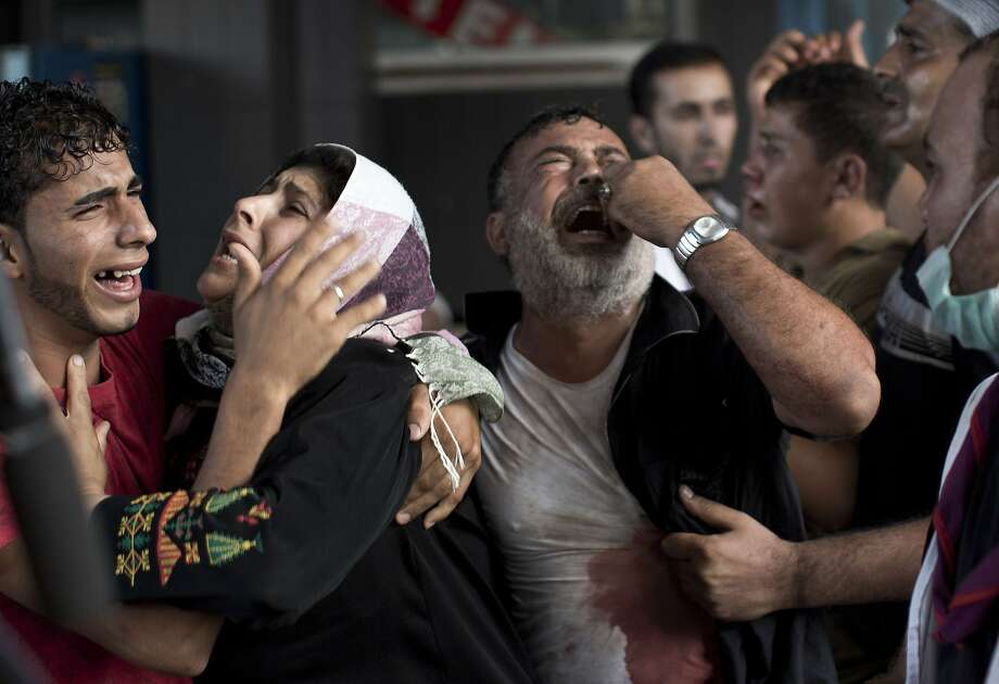 TOPSHOTS Palestinian mourners cry at Gaza City's al-Shifa hospital after an explosion killed at least seven children in a public playground in the beachfront Shati refugee camp on July 28, 2014. Palestinian medical sources blamed the killings on air strikes launched by the Israeli military, which in turn said Hamas had misfired its own rockets at the camp and at the Shifa hospital.  AFP PHOTO/MAHMUD HAMSMAHMUD HAMS/AFP/Getty Images Photo: Mahmud Hams, AFP/Getty Images