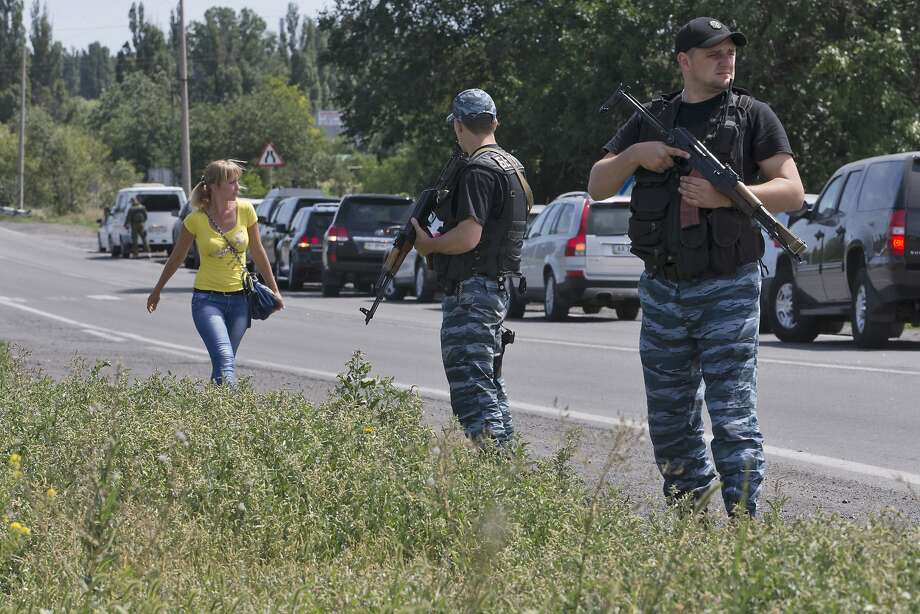 Self-proclaimed Donetsk People's Republic officers guard a convoy of police and forensics experts. Photo: Dmitry Lovetsky, Associated Press