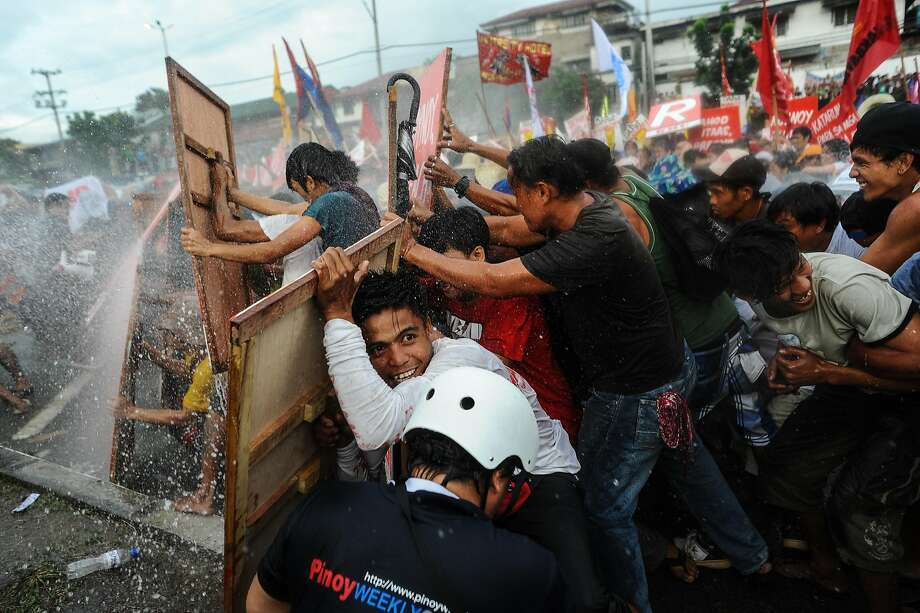MANILA, PHILIPPINES - JULY 28:   Protestors barricade themselves against water cannon spray during President Benigno Aquino's annual State of the Nation Address on July 28, 2014 in Manila, Philippines. Thousands of government protestors staged a rally to protest the alleged corruption of Aquino involving the Disbursement Allocation Programme, a 145-billion-peso ($3.34-billion) fund to boost public spending but some of the funds went to favored allies in the Lower House of Representatives, reports say.  (Photo by Dondi Tawatao/Getty Images) *** BESTPIX *** Photo: Dondi Tawatao, Getty Images