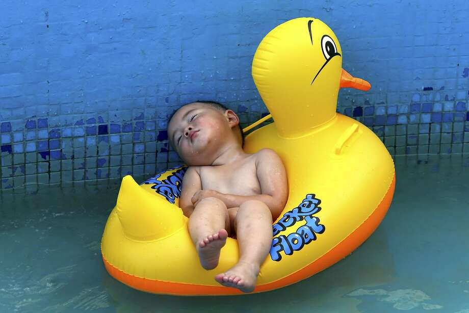 Nap on a raft: A rubber ducky buoys a baby in Daying county, southwest China's Sichuan province. Photo: Associated Press