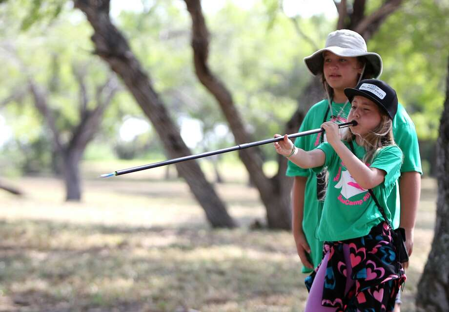 Waiting to exhale:Olivia Saldana, 11, prepares to blow a dart at a target as her friend   Katie Gueller watches at the Flint Hills Resources' Wildlife Learning Preserve in Corpus Christi.   The girls were studying about wetlands and wildlife habitat at Texas State Aquarium SeaCamp. Photo: Rachel Denny Clow, Associated Press