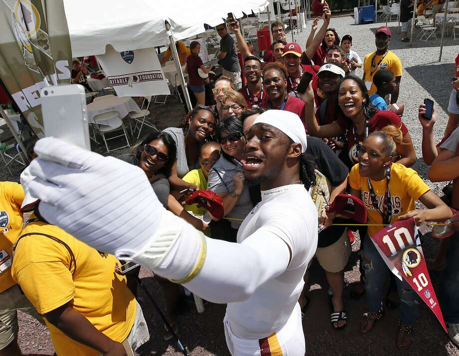 Washington Redskins quarterback Robert Griffin III takes a selfie with a group of fans after practice at the team's NFL football training facility, Monday, July 28, 2014 in Richmond, Va. (AP Photo/Alex Brandon) Photo: Alex Brandon, Associated Press